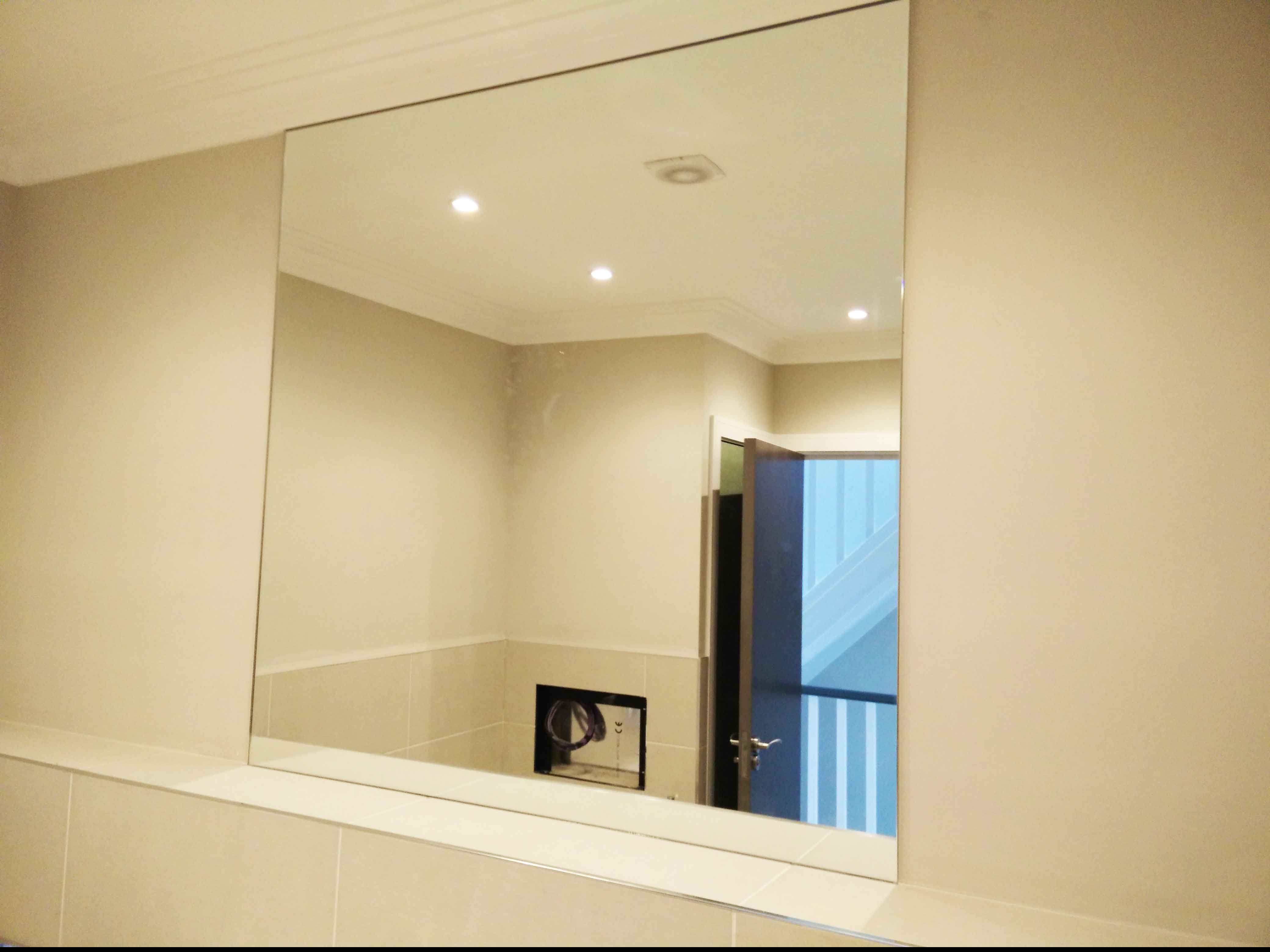 Glass mirror with heat pad for demisting